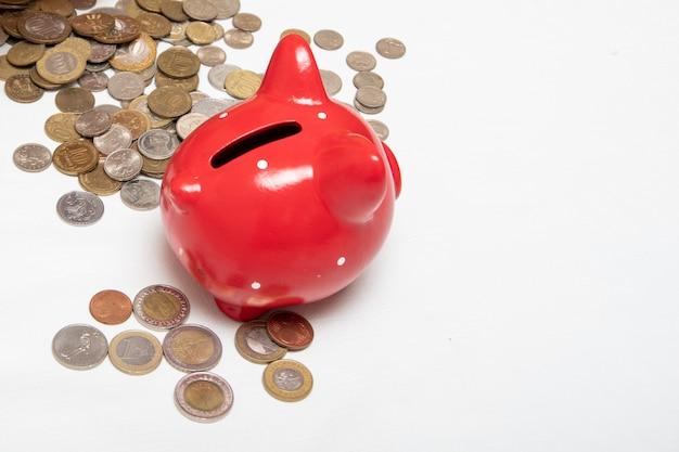 빨간 돼지 저금통 근처의 탁자에는 여러 나라의 많은 동전들이 놓여 있습니다. 금융 개념입니다.
