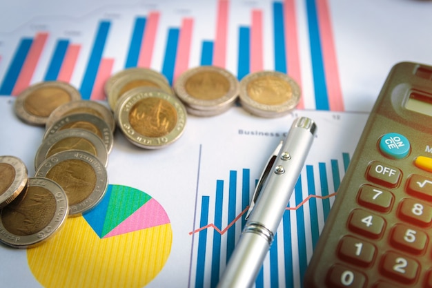 Many coins with pen and calculator on business chart