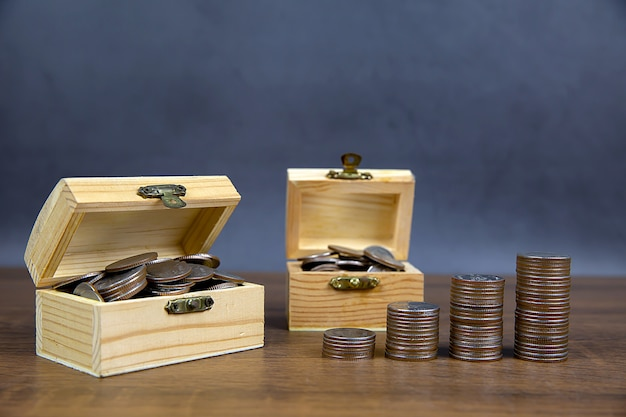 Many coins in a wooden crate for money saving ideas and financial planning insurance.