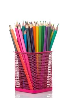 Многие цветные карандаши в розовом стекле на белом изолированном фоне. крупный план.