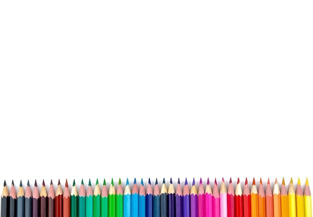 Многие цветные карандаши на белом изолированном фоне. крупный план. вид сверху. канцелярские товары. место для текста