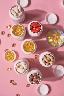 분홍색 배경에 많은 색 알약 캡슐 비타민. 건강에 좋은 보충제 및 의약품