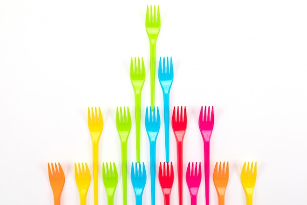 Many color plastic forks on a bright background