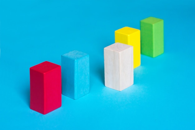 Many colored blocks in a row and one wooden block on blue background