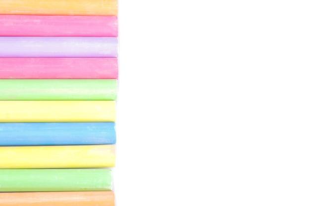 격리된 흰색 배경에 한 줄로 누워 있는 많은 색깔의 어린이 크레용