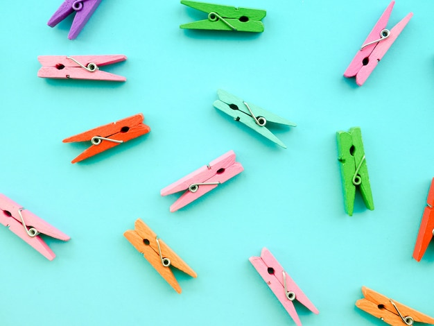 Many colored clothespins on a blue background.