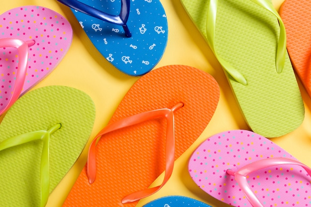 Many colored flip flops on yellow background. copy space top view
