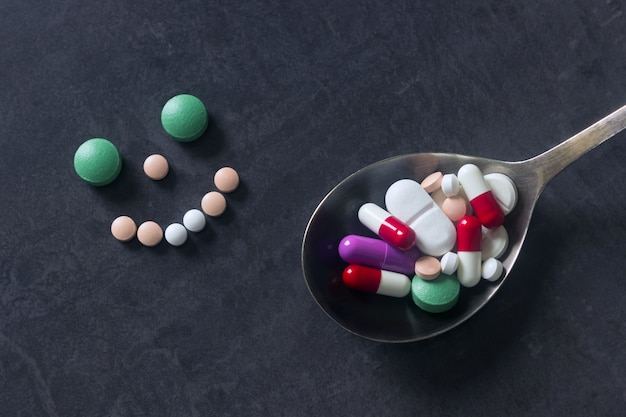 Many colored pills and tabs with spoon on a dark background