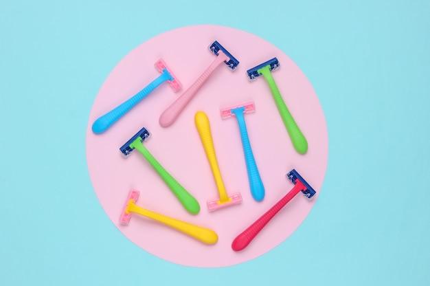 Многие цветные пластиковые бритвы на синем фоне с розовым пастельным кругом. минималистичный натюрморт красоты