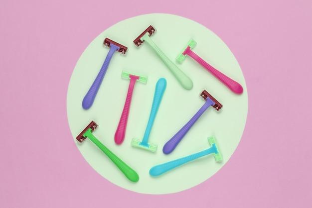 Многие цветные пластиковые бритвы на розовом фоне с зеленым пастельным кругом. минималистичный натюрморт красоты