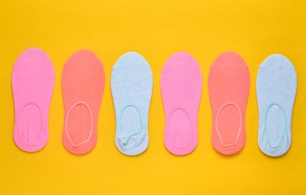黄色の背景に多くの色の靴下