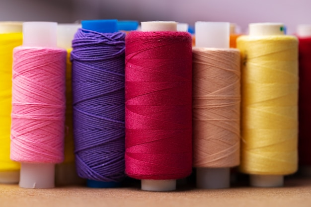Many colored spools of threads as a surface