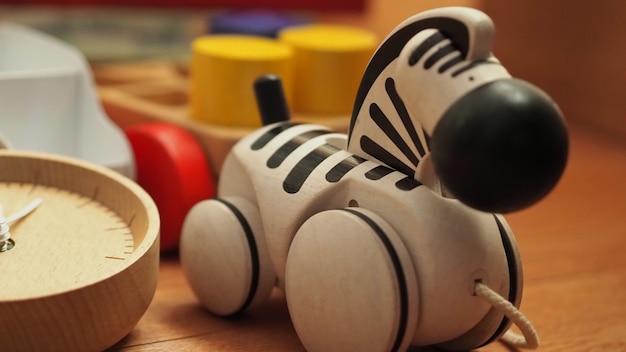 Множество красочных детских деревянных игрушек на светло-коричневом ковре, в том числе автобус с мячом и другие
