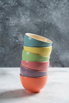 Many of colorful bowls on gray .