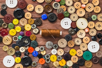Many colorful buttons; brown thread and needle on wooden background