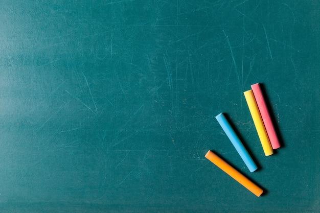 많은 다채로운 초 및 칠판 배경에 고립