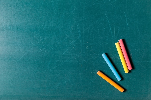 Many colorful chalks and isolated on blackboard background