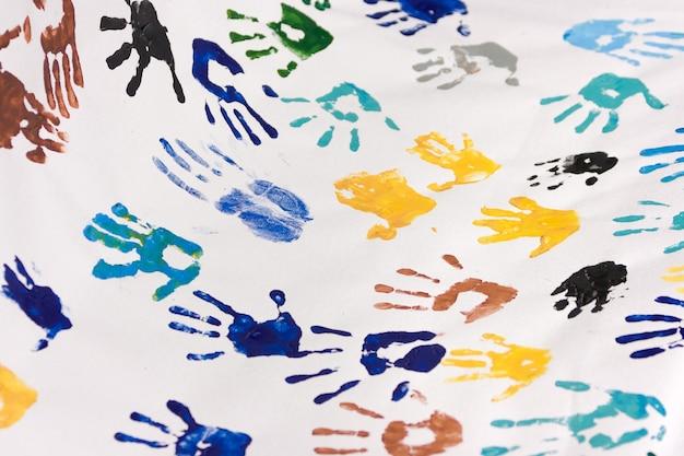 白い紙に多くのカラフルな子供の手形