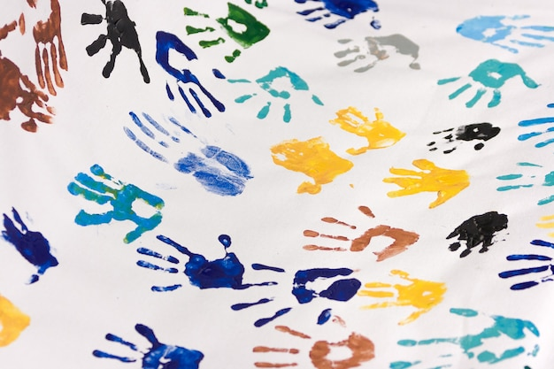Many colorful childrens handprints on white paper