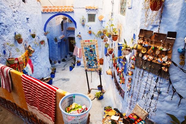 모로코에서 어딘가에 거리의 파란색 벽에 많은 화려한 장식이 걸려