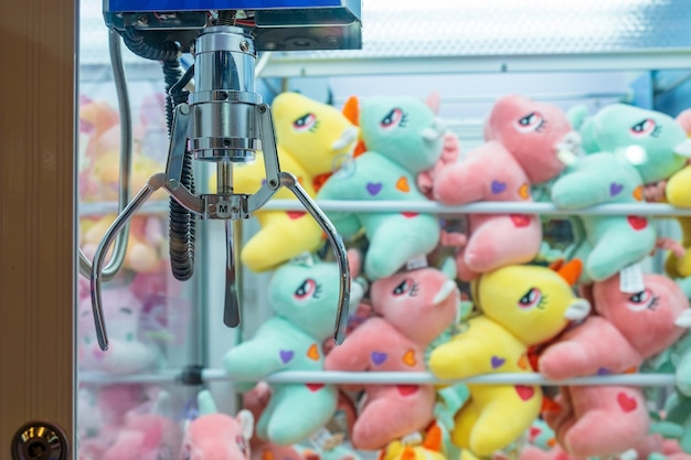 Many colorful dolls put in the cabinet claw game wait for people play catching.