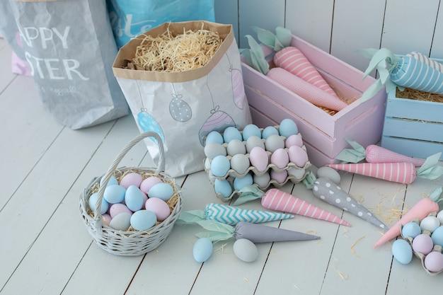 Многие красочные пасхальные яйца и корзины с морковью на деревянном полу украшение пасхальной комнаты