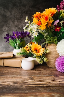 Many colorful flowers in the vase with gift boxes on wooden table