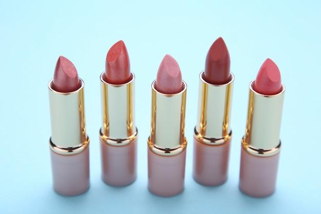 Many colorful lipstick on blue background, close up