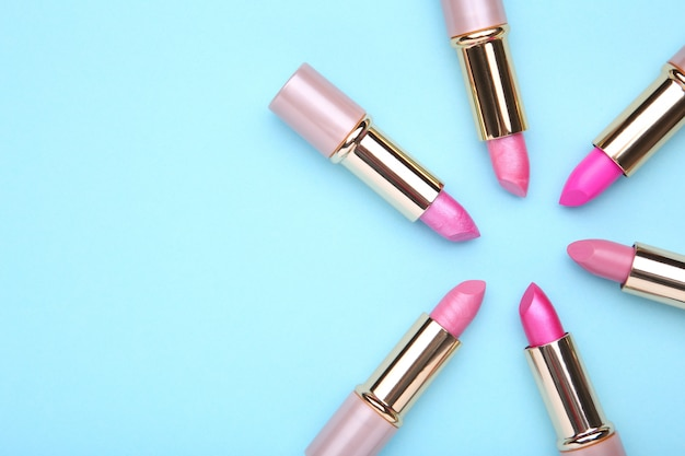 Many colorful lipstick on blue background, flat lay