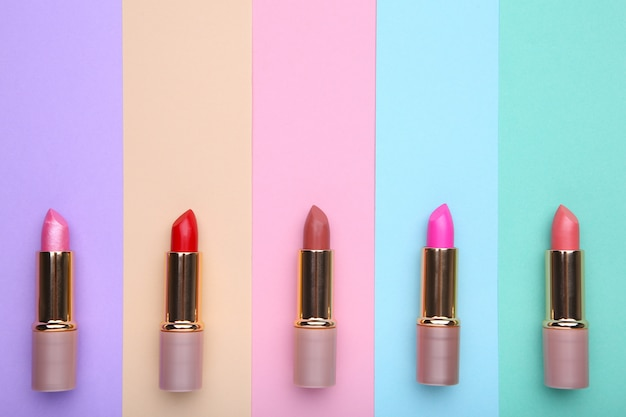 Many colorful lipstick on colorful background, flat lay
