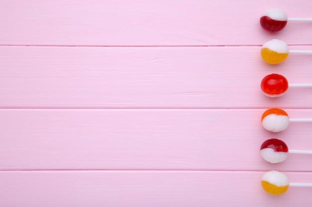 Много красочный леденец на палочке на розовой предпосылке. концепция сладких конфет