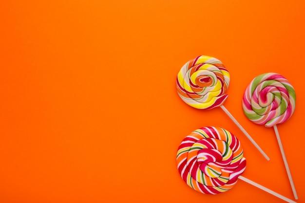 Many colorful lollipops on orange background, sweets