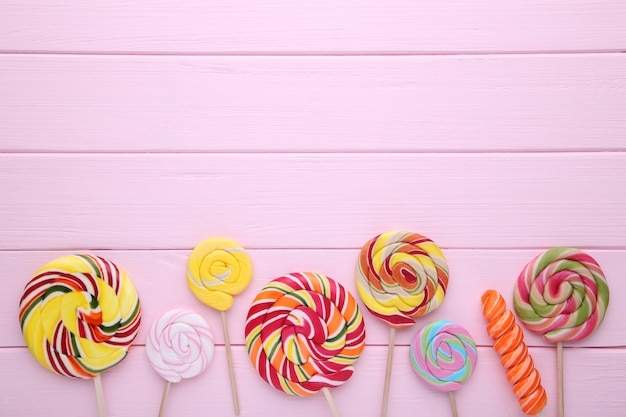 Many colorful lollipops on pink wooden background.