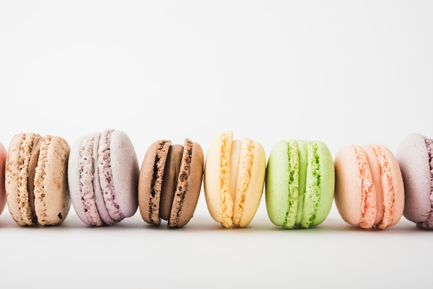 Many colorful macaroons on white backdrop
