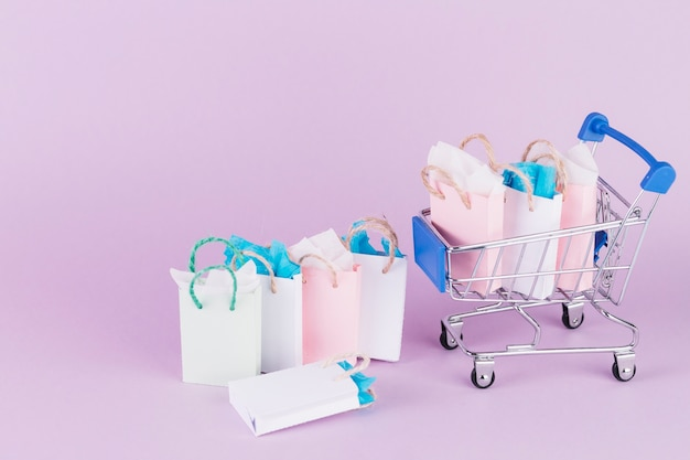 Many colorful paper shopping bags in cart on pink background