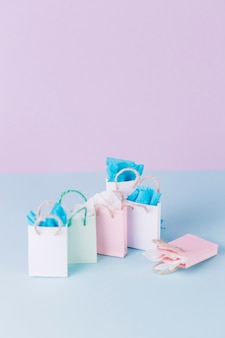 Many colorful paper shopping bags on blue surface