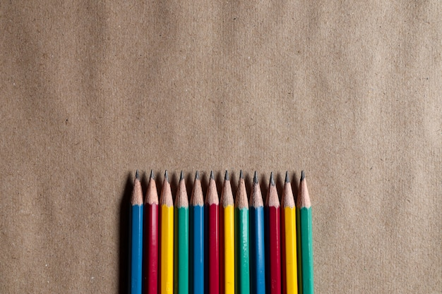 Many colorful pencils on brown paper can be applied to designs.