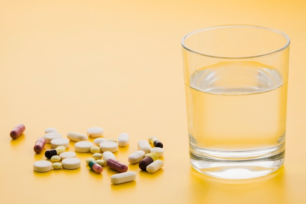 Many colorful pills and glass of water on yellow background
