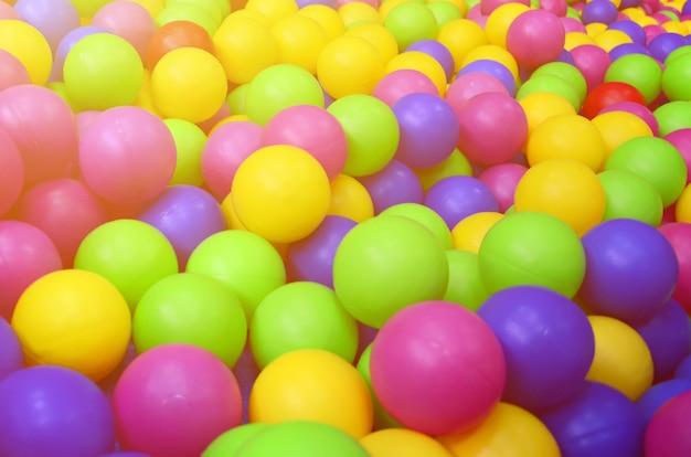 놀이터에서 아이들의 겨드랑이에 많은 다채로운 플라스틱 공. 패턴을 닫습니다
