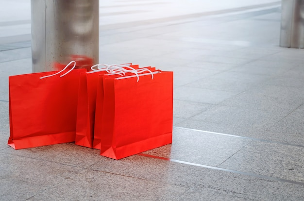 Many colorful red paper shopping bags on floor