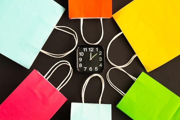 目覚まし時計の周りの多くのカラフルなショッピングバッグ