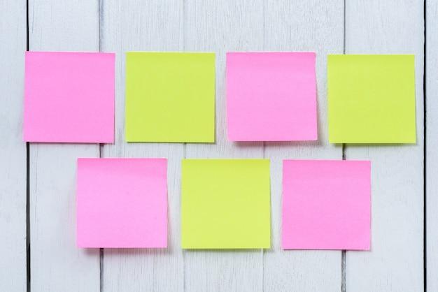 많은 다채로운 스티커 메모, 흰색 나무 빈티지 배경에 참고 게시.