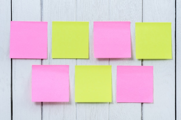 Many colorful sticky note, post note on white wooden vintage background.