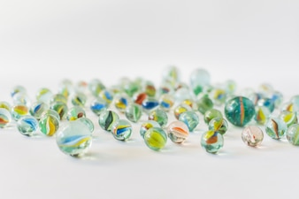 Many colorful transparent marbles on white background