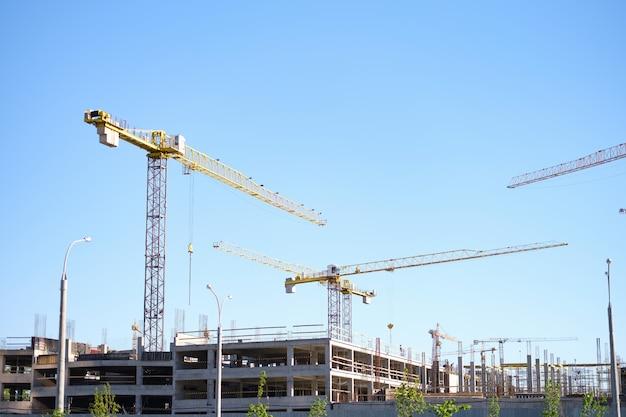 현장 배경에서 다층 건물 근처에 서 있는 많은 건설 크레인