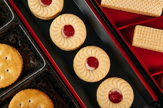 Many cookies are beautifully arranged in a plate and then placed on a wooden table.