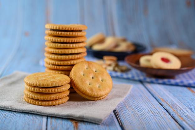 多くのクッキーは生地に置かれ、木製のテーブルに置かれます。