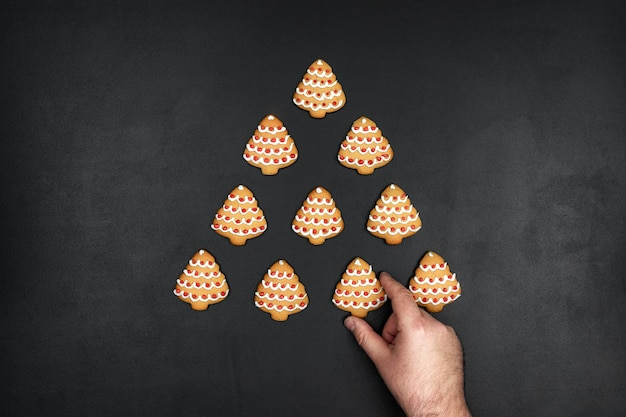 Many cookies shaped christmas tree on a black chalkboard background, minimalistic new year concept with a hand