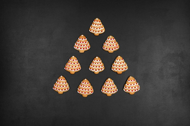 Many cookies shaped christmas tree on a black chalkboard background, minimalistic new year concept