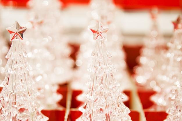 Много хрустальных маленьких декоративных елок в красной коробке в магазине. рождественская ярмарка. закройте вверх.